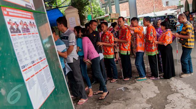 Sejumlah penyandang disabilitas berjalan memasuki TPS 07 Kelurahan Cawang untuk menggunakan hak pilih pada Pilkada Gubernur dan Wakil Gubernur DKI Jakarta Tahun 2017 di Jakarta, Rabu (15/2). (<a href:http://photo.liputan6.com/news/antusias-penyandang-disabilitas-coblos-pilkada-dki-2017-2856864>Liputan6.com</a>/Gempur M Surya)